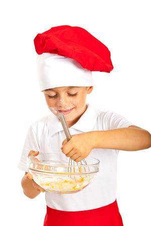 Smiling chef boy mixing dough isolated on white background photo