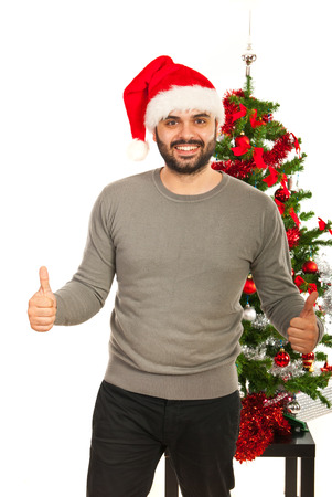 Cheerful Christmas man giving thumbs up in front of tree photo
