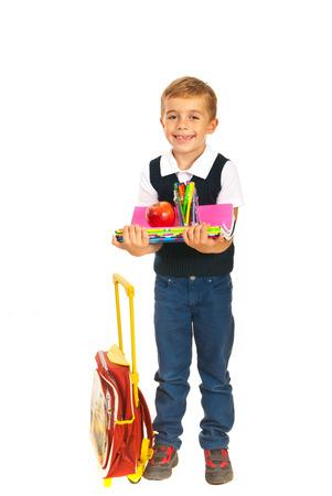 Happy school boy holding notebooks,pencils and apple photo