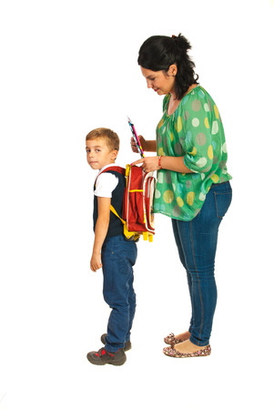 Mother prepare boy for school and giving notebooks isolated on white background photo