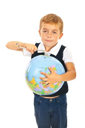 Little boy holding tool key and fixing world globe isolated on white background photo