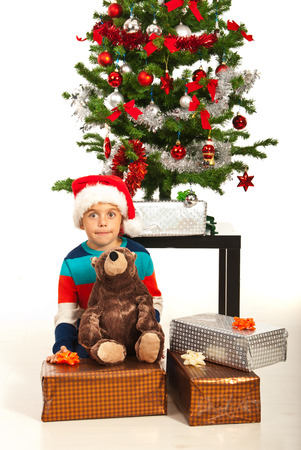 Amazed little boy with Christmas presents in front of tree photo