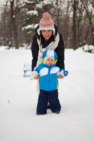 Mother helping baby to make first steps in the snow  photo