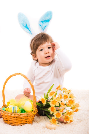 Ester bunny baby with basket with eggs and flowers sitting on carpet photo