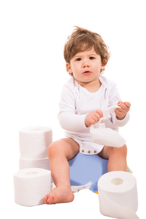 Upset baby boy sitting on potty with rolls of toilet paper around him photo