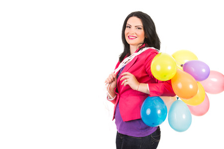 Happy woman standing in profile and holding many balloons on her shoulder isolated on white background photo