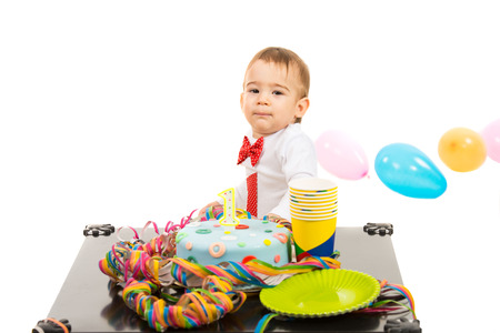 Boy at first anniversary with colorful cake and balloons standing at table isolated on white background photo