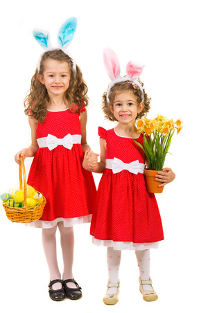 Happy two sisters with bunny ears holding hands and holding basket with easter eggs and daffodils flower isolated on white background photo