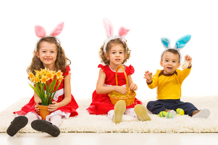 Happy kids with bunny ears sitting on carpet and holding easter eggs and flowers photo