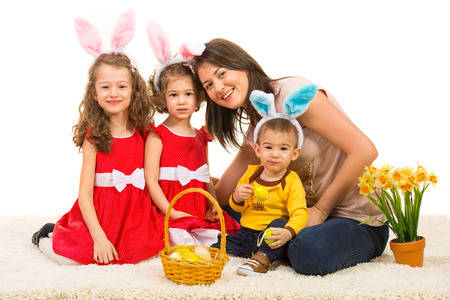 Happy mother with her kids wearing bunny ears sitting together on fur carpet photo