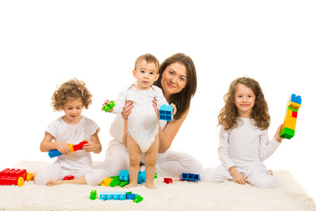 Family of mother with three kids playing with building blocks home and sitting on carpet photo