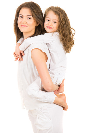 Mother giving piggyback ride to her daughter and being in motion isolated on white background photo