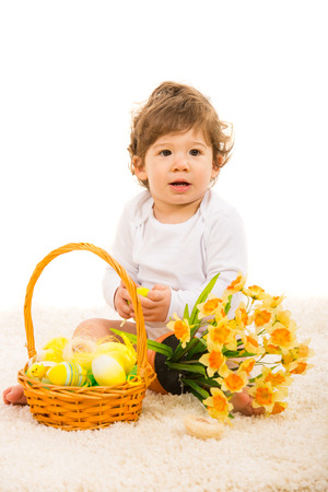 Baby boy sitting on fur carpet with basket with Easter eggs and daffodils photo