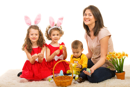 Happy mom and kids sitting on carpet with Easter basket and spring flowers photo