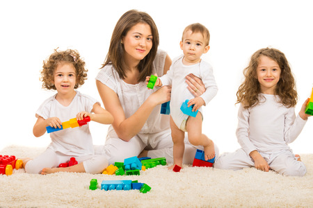 Happy family playing hom and sitting together on the carpet against white background photo