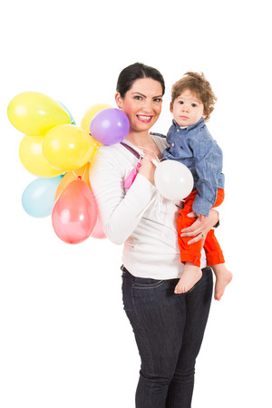 Happy mother holding toddler boy and many balloons isolated on white  photo