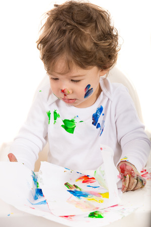 Toddler boy painting and sitting in chair against white  photo