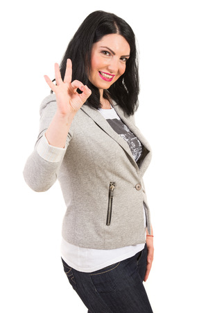 Successful casual woman showing okay sign hand gesture isolated on white  photo