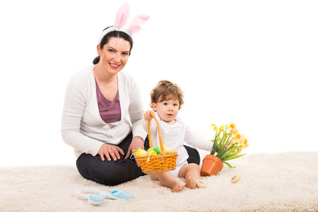 Mother and toddler sitting on fur carpet and boy giving Easter basket with eggs photo