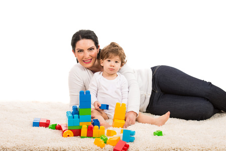 play blocks: Mother and her son boy sitting on fur carpet and playing with building bricks isolated on white