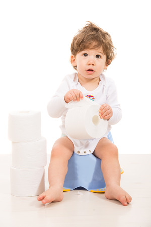 Amazed boy sitting on potty and holding rolls of paper against white  photo