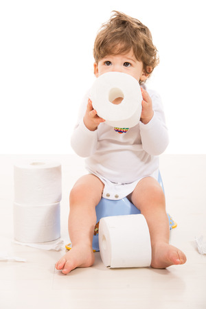Toddler boy sitting on potty holding rolls paper and looking up  Foto de archivo