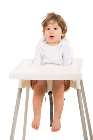high chair: Amazed toddler boy standing straight in  high chair isolated on white  Stock Photo