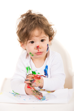 Amazed messy toddler boy with paints on his face and hands photo