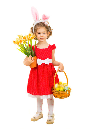 Beautiful girl with bunny ears holding basket with Easter eggs and daffodils isolated on white background photo