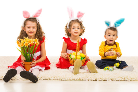 Happy three brothers sitting in a line on carpet and holding Easter eggs and flowers photo