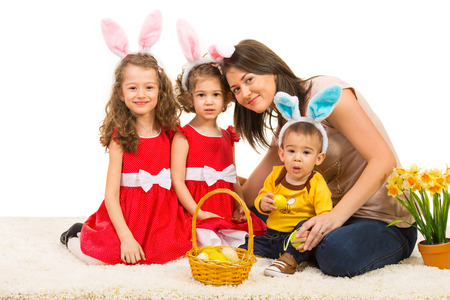 Beauty mother and  kids with bunny ears sitting on carpet with Easter basket photo