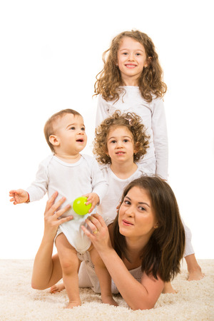 Happy mother and kids with daughter on top each other and mother holding toddler boy photo