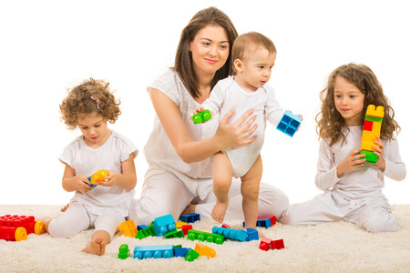 Beauty mom playing with her three kids home and sitting together on fur carpet photo