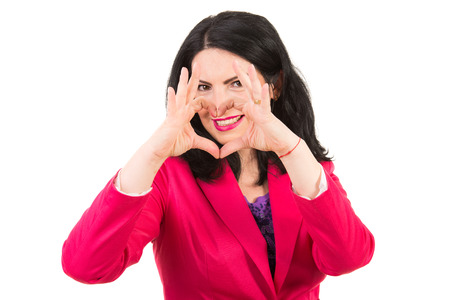 Woman heart shape with fingers in front of her smile isolated on white background photo