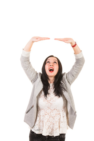 Amazed woman holding copy space over head isolated on white background photo