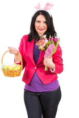 Beauty spring woman with bunny ears holding Easter basket and flowers photo