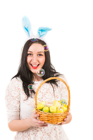 blowing out: Cheerful woman with bunny ears holding Easter basket and bubbles of soap are blowing out Stock Photo