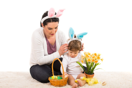 Mother put bunny ears to her son and prepare a Easter basket  photo