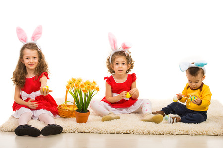 Happy three kids with bunny ears and Easter eggs  sitting on carpet home photo