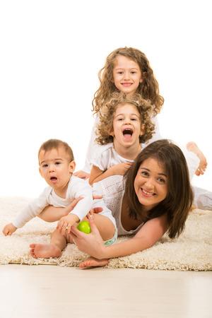 hermanos jugando: La madre y sus tres hijos se divierten en casa Foto de archivo