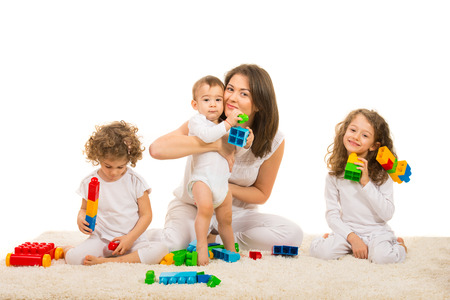 Happy mom and kids playing with building blocks home and sitting together on carpet photo