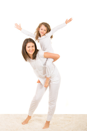 piggy back: Mother and daughter having fun home and offering to her girl piggy back ride