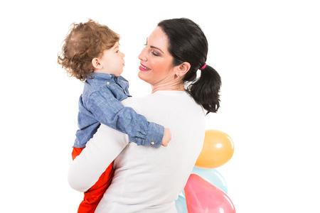 Back of mother looking to toddler boy and holding balloons isolated on white background photo