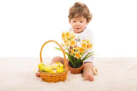 Toddler boy with Easter basket arrange narcissus in a pot and sitting on carpet photo