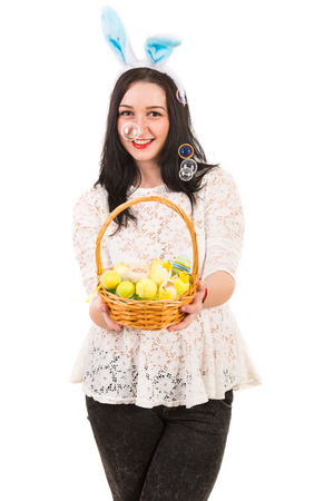 blow out: Happy woman with blue bunny ears holding Easter basket and soap bubbles being blow out against white background Stock Photo