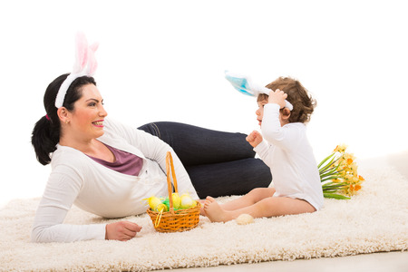 Happy mother and toddler boy with bunny ears sitting on carpet with Easter basket photo