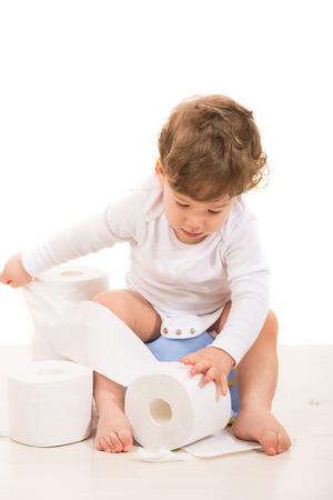 Jongen van de peuter op onbenullig scheur wc-papier tegen een witte achtergrond