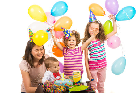 First  birthday party of boy celebrate with his family ,mother and sisters with cake and balloons photo