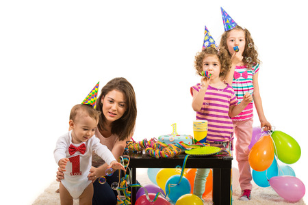 Mother and kids having party and celebrate  boy first birthday,toddler trying to catch soap bubbles photo