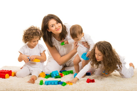 Beauty mom playing with her kids home and sitting together on fur carpet photo
